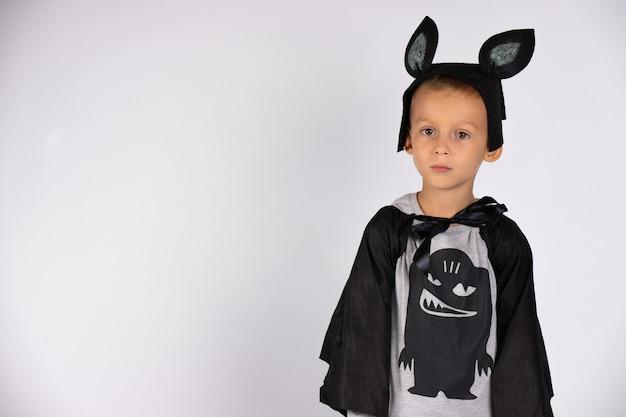 Скромный мальчик в костюме летучей мыши. карнавальный костюм. концепция праздника. белая изолированная стена с боковым пустым пространством.