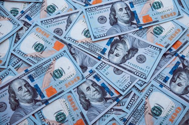 Разбросано сотня американских банкнот. наличные стодолларовые банкноты, доллар фоновое изображение.