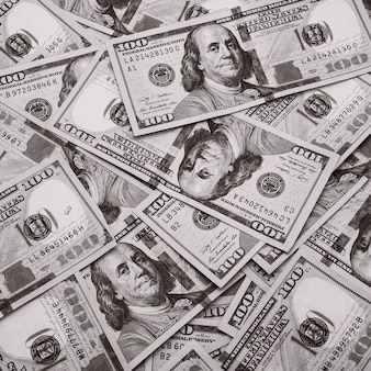 100枚のアメリカの紙幣が散らばっています。現金百ドル札、ドルの壁の画像。