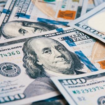 100枚のアメリカの紙幣が散らばっています。百ドル札を現金化する
