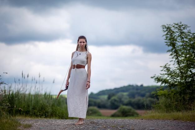 Венгерка в льняном платье с бантом стоит на дороге