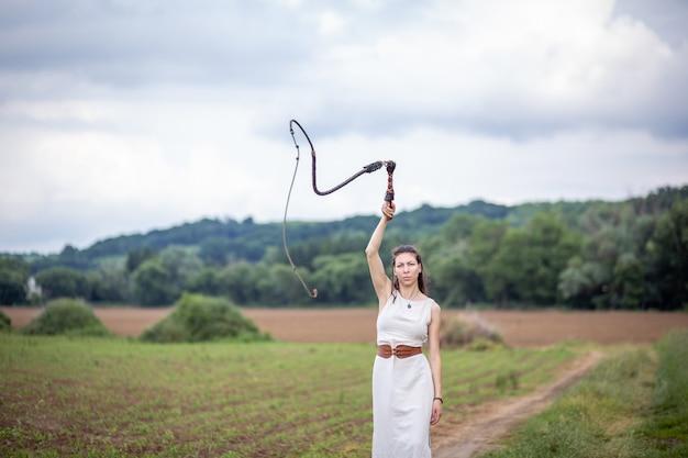 Венгерка стоит на поле в льняном платье с кнутом