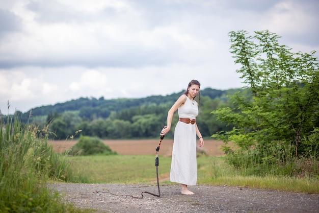 Венгерка стоит на дороге в льняном платье с кнутом