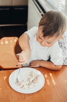 Голодный ребенок ест пельмени на кухне, сидя в кресле в белой футболке