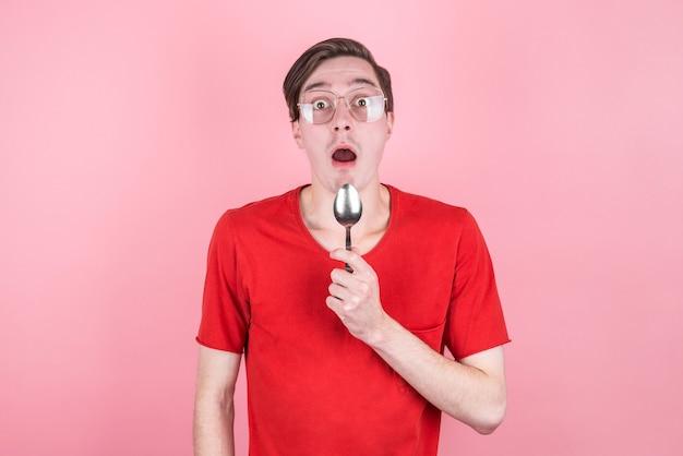 배고픈 남자가 숟가락을 손에 들고 놀라서 맛있는 음식을 생각합니다