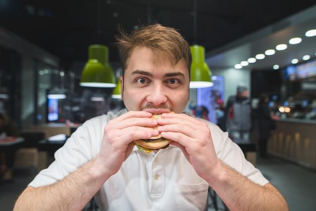 Голодный мужчина с бородой жадно ест гамбургер и смотрит в камеру. быстрое питание в бистро