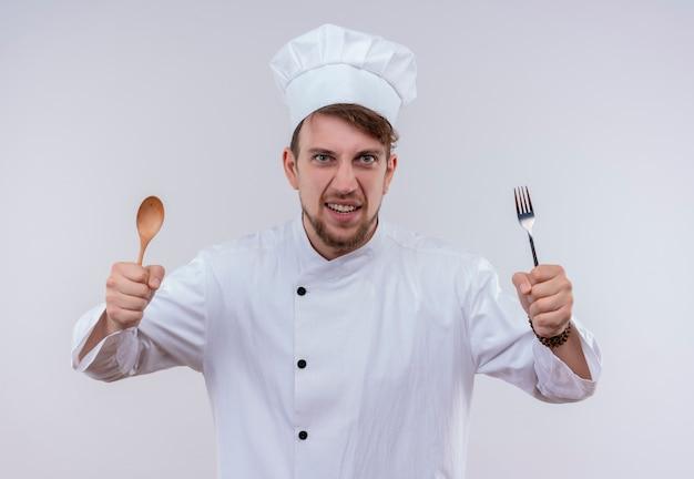 Голодный молодой бородатый шеф-повар в белой униформе и шляпе держит деревянную ложку и вилку, глядя на белую стену