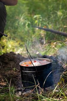 自然の中でハンターが山高帽でシュルパを火で調理