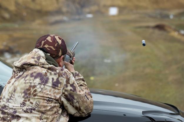 사격장에서 위장을 한 사냥꾼이 무기를 보정합니다. 한 남자가 목표물을 쏘고 있습니다.