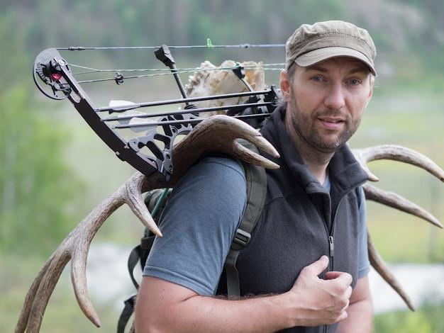Охотник с луком в лесу несет на спине лосиные рога и смотрит в камеру.