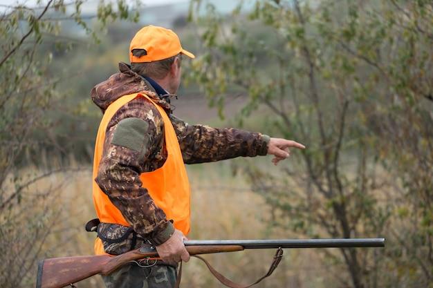 Охотник с ружьем в руках в охотничьей одежде в осеннем лесу в поисках трофея