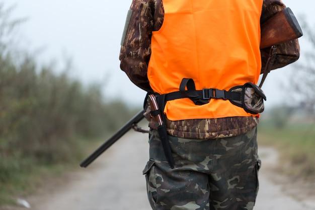 트로피를 찾아 가을 숲에서 사냥복을 입고 손에 총을 든 사냥꾼