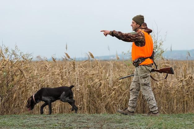 トロフィーを求めて秋の森で狩猟服を手に銃を持ったハンター