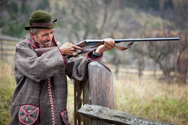Охотник в охотничьей одежде с ружьем в руках целится