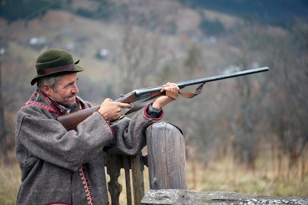 사냥 옷을 입은 손에 총을 든 사냥꾼이 조준하고 쏠 준비가되어 있습니다.
