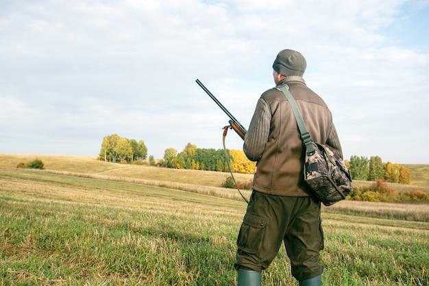 Охотник с ружьем в руках для охоты в осеннем лесу и поле