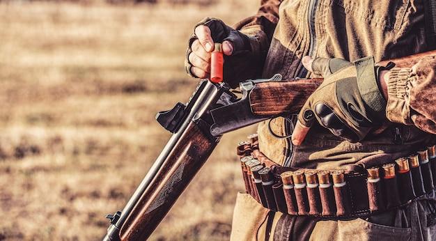 가을 숲에서 사냥을 하기 위해 사냥총과 사냥 형태를 하고 있는 사냥꾼. 남자는 사냥 중입니다. 헌터맨. 사냥 기간, 가을 시즌. 총을 든 남자.