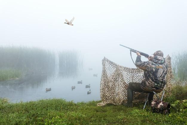 가을철 오리를 사냥하기 위해 사냥총과 사냥형태를 하고 있는 사냥꾼. 사냥 기간. 남자는 사냥 중입니다. 헌터맨.