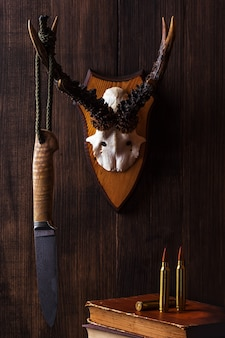 ダマスカス鋼で作られた狩猟用ナイフが鹿の角にぶら下がっています。
