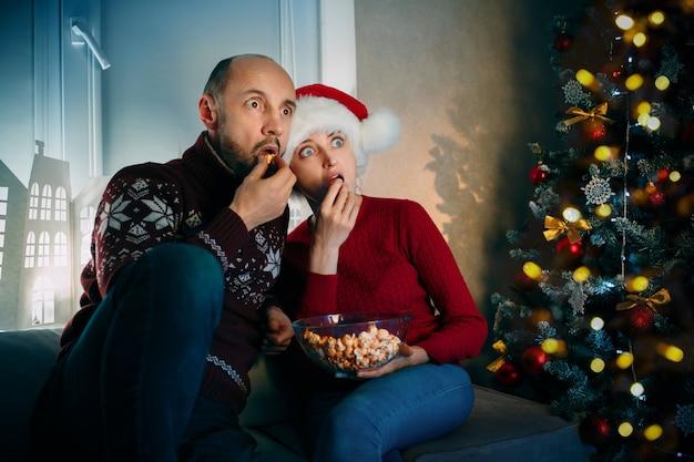 夫と妻はクリスマスイブにテレビを見ながらポップコーンと驚きを楽しんでいます