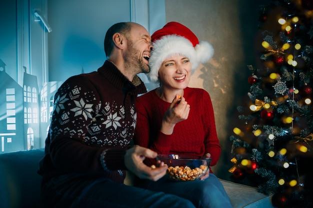 夫と妻はクリスマスイブにテレビを見ながら大声で笑いながらポップコーンを楽しんでいます
