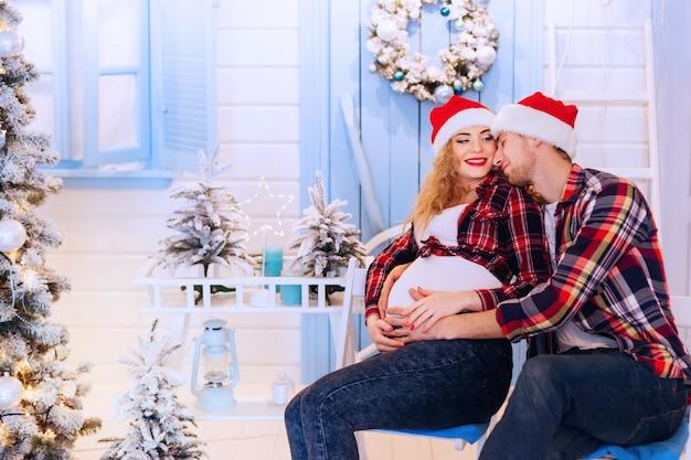 青と白の新年の風景を背景に夫が妊娠中の妻を抱きしめる