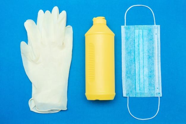 Гигиенический набор одноразовых резиновых перчаток флакон антисептического дезинфицирующего средства и медицинская маска на синем фоне