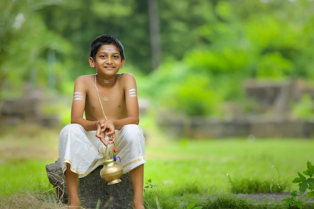 聖水ポットを持つインドの僧侶の子供