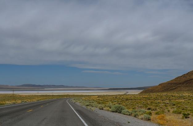 늦여름 날 여행자의 구분선이있는 주간 고속도로. 미국 고속도로 농촌 중서부 필드