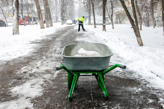 Дворник моет тротуар и насыпает соль.