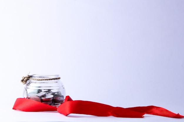 Кувшин с серебряными монетами, перевязанными небольшими веревками и украшенными красными лентами.