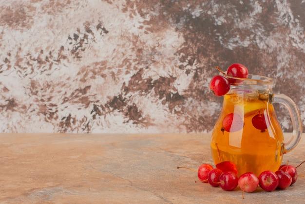 Банка сока, украшенная вишневыми яблоками на мраморном столе.