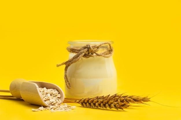 黄色の背景に木製のスクープの牛乳とオーツ麦フレークの瓶