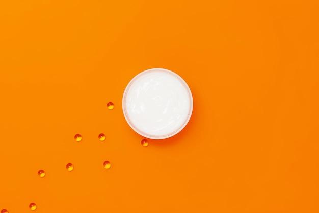 Баночка увлажняющего белого крема на оранжевом фоне, рядом с которой капсулы с витамином е.