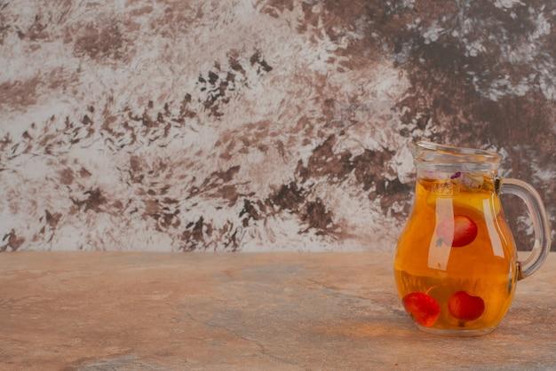 大理石のテーブルにさくらんぼと桃ジュースの瓶。