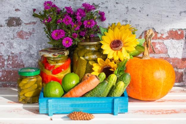 Банка маринованных огурцов и свежесобранных овощей. перец баклажан и помидоры