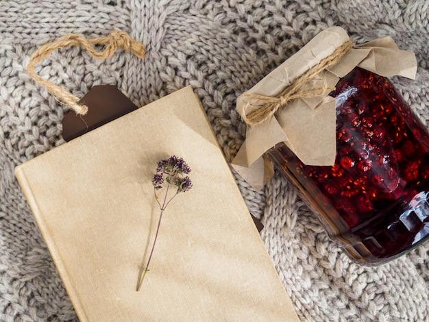 Баночка с малиновым вареньем, книга и веточка душистых на шерстяном одеяле