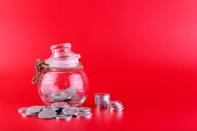 Банка с монетами внутри и много монет, лежащих вне банки, изолированные на красном фоне