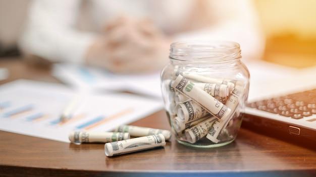 テーブルの上に丸められた紙幣が入った瓶。ノートパソコン、論文、背景の女性