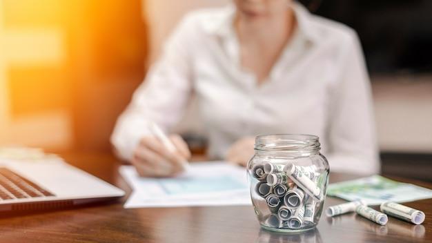 Банка с свернутыми банкнотами на столе. ноутбук, документы, женщина на заднем плане