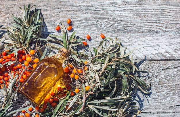 シーバックソーンオイルと木製の背景にベリーとシーバックソーンの新鮮な枝の瓶