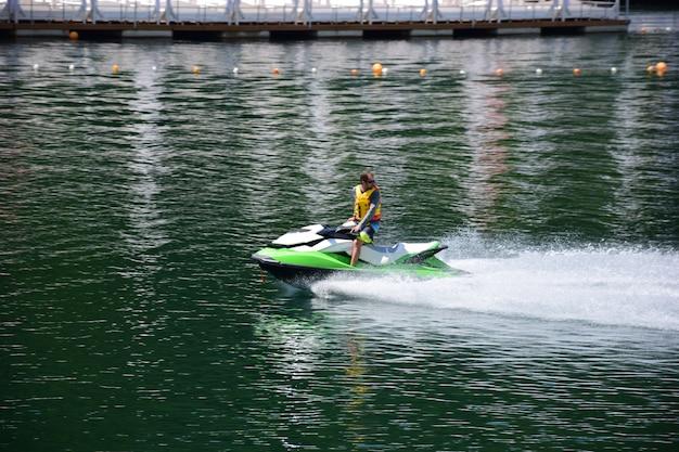 Гидроцикл, на котором плывет человек в спасательном жилете, быстро мчится по воде