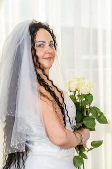 ユダヤ人の花嫁が、白いバラの花束を手に、腰に写真を添えて、フッパー式の前にホールに立っています。縦の写真