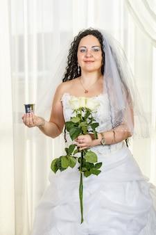 ユダヤ人の花嫁が、白いバラの花束とグラスワインを片手に、フッパー式の前にホールに立っています。