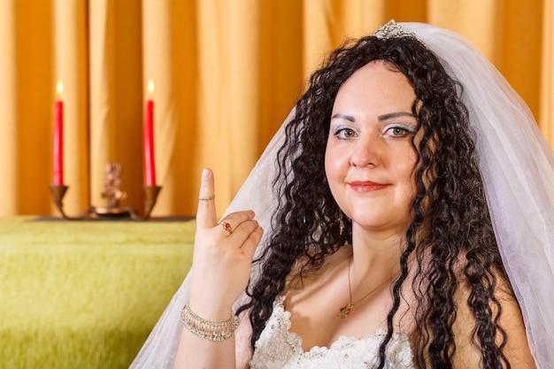 베일이 달린 하얀 웨딩 드레스를 입은 유대인 신혼 부부가 추파 의식이 끝난 후 꽃이있는 테이블에 앉아 검지에 반지를 보여줍니다.