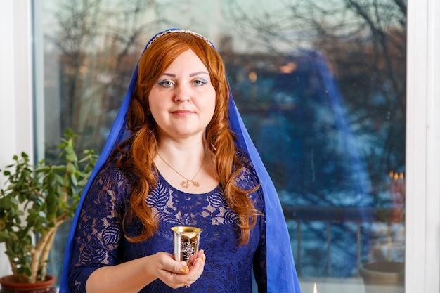 過ぎ越しの祭りのセダーのテーブルで青い岬に頭をかぶったユダヤ人の女性がワインをキッドゥーシュします