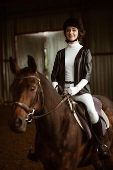 Девушка-жокей в парадном костюме сидит на коне изобразила фрагмент тела девушки, намордник лошади и бр ...
