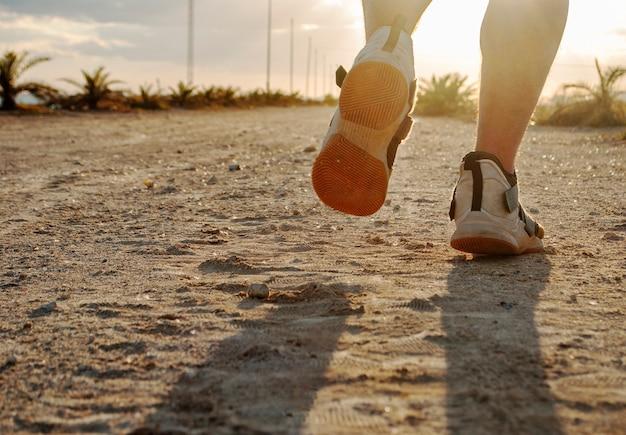 저녁에 조깅하거나 남자가 석양에 해변의 길을 따라 달린다.