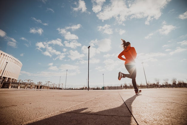 Бегущая женщина бежит по улице.