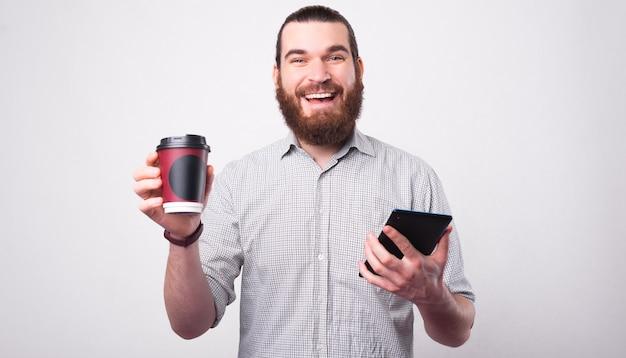 うれしそうなあごひげを生やした男が彼のコーヒーと彼のコーヒーブレイクをカメラに向かって微笑んでいるタブレットを持っています